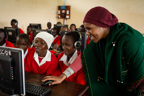 Teacher and students looking at a computer monitor