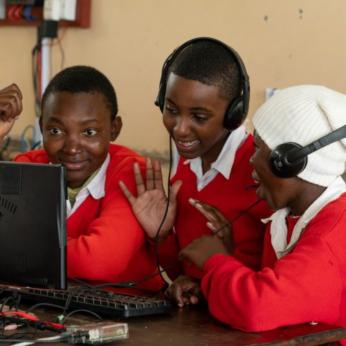 Students smiling while looking at a computer screen